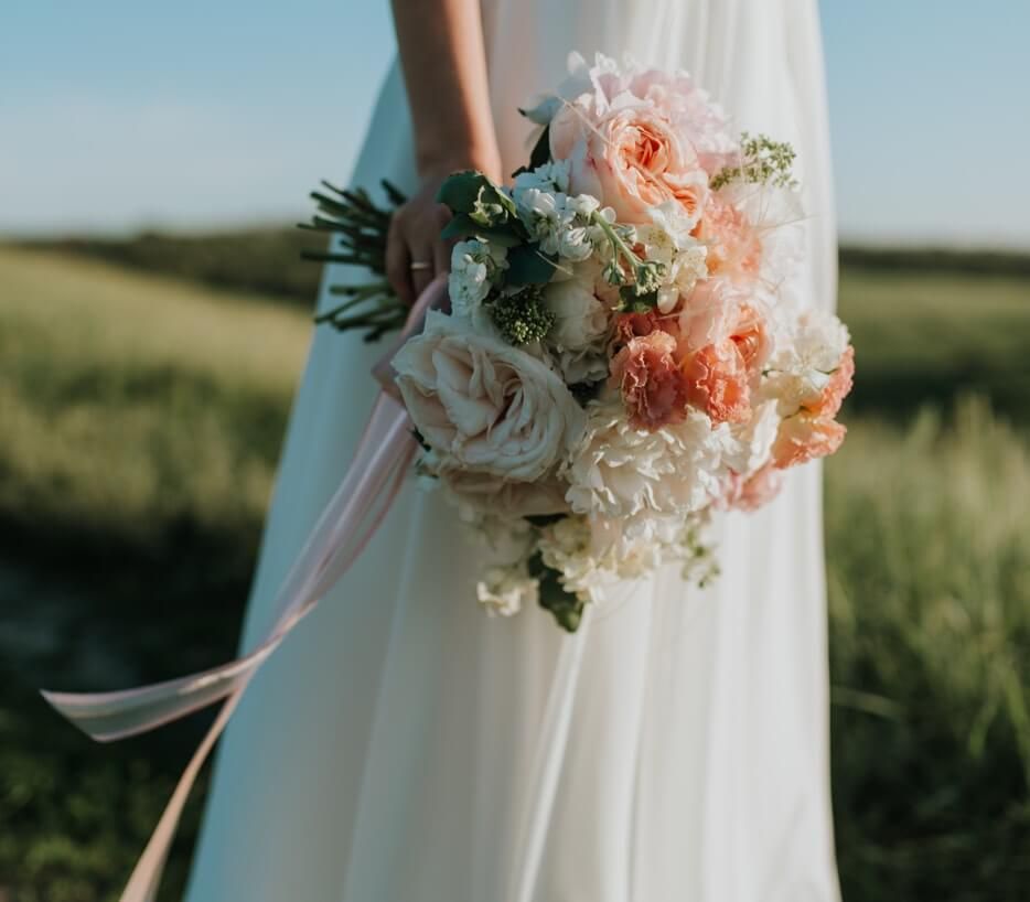 Bride wearing a white gown holding a flower bouquet